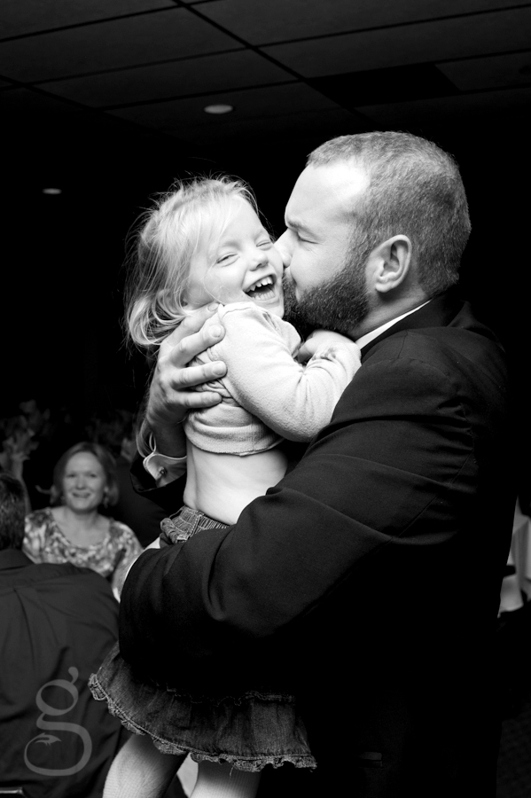 the groom kissing his new niece as she giggles at the reception.