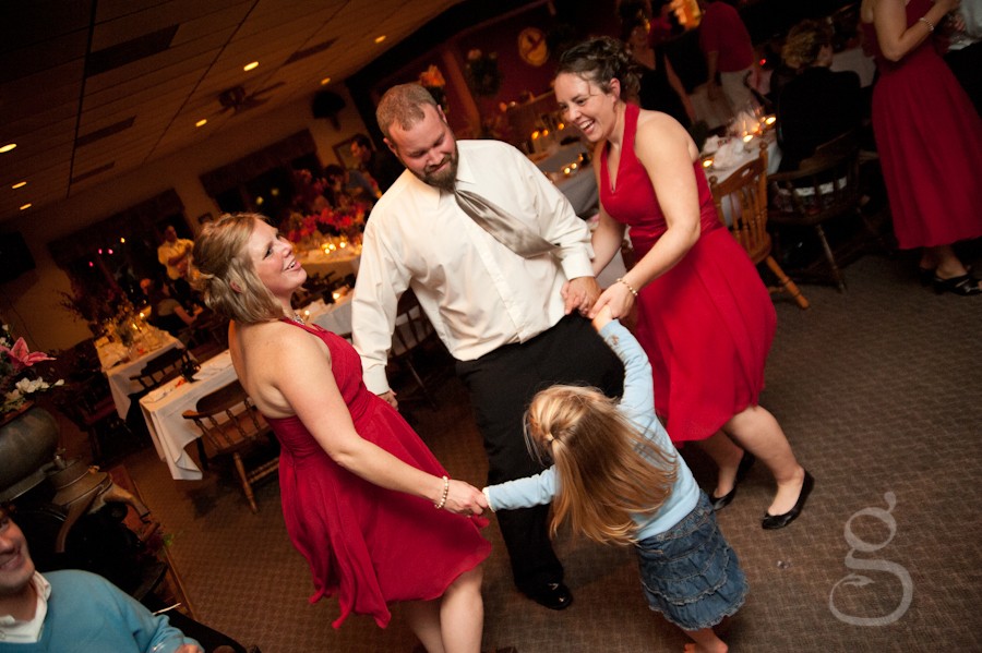the groom dancing in a circle with the bridesmaid's and niece.
