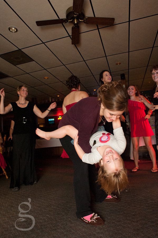 little girl being dipped on the dance floor with her hair flying.