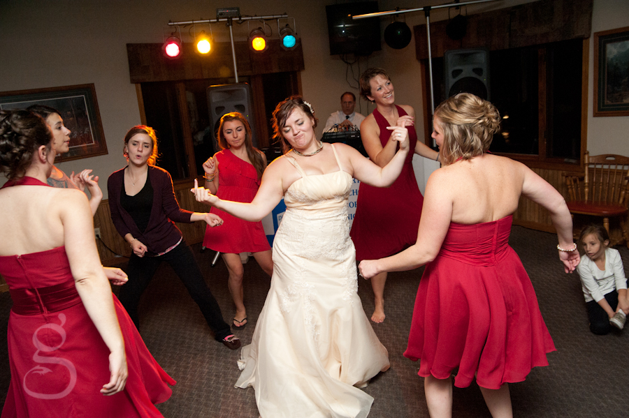 bride and bridesmaids dancing in a circle on the dance floor.