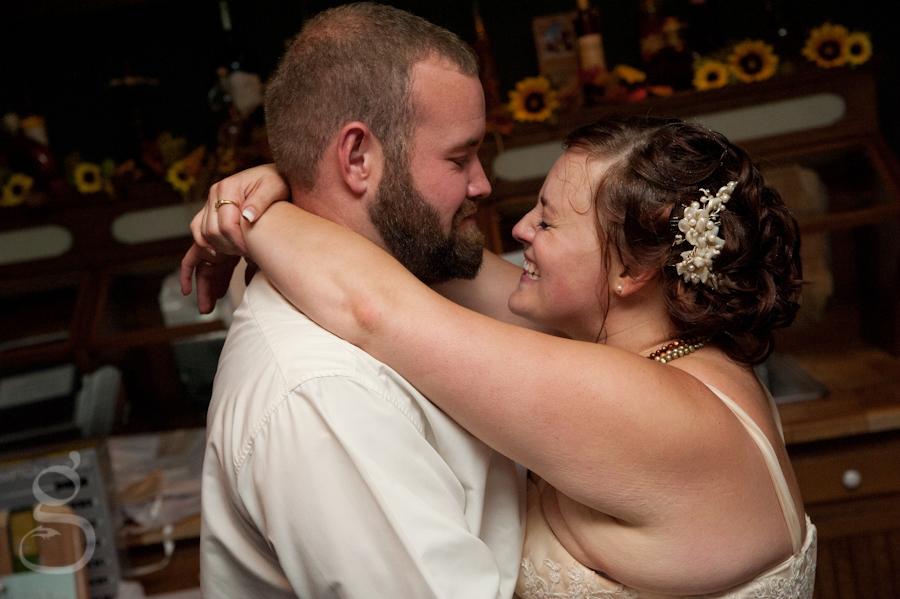 bride and groom smiling at one another on the dance floor.