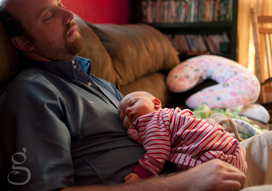 father and newborn daughter asleep on the couch in the afternoon light.