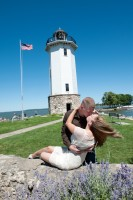 Couple kissing with the lighthouse in the background and the wind whipping her hair around.