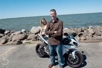 Couple posing with motorcycle in front of the lake.