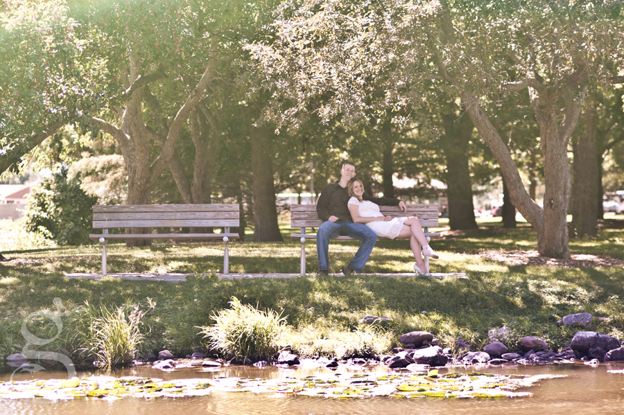 Couple leaning into each other on the park bench looking out across the pond.