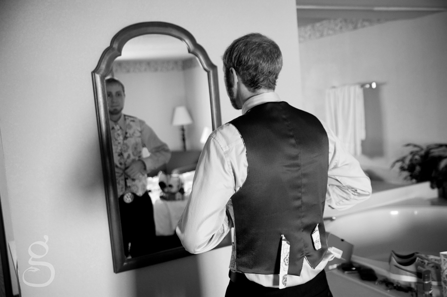 the groom getting his vest and tie arranged for the wedding.