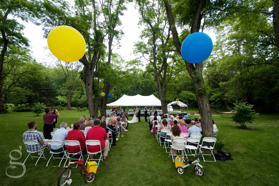 giant balloons and vintage trikes marking the aisle for the bride and groom to walk down.