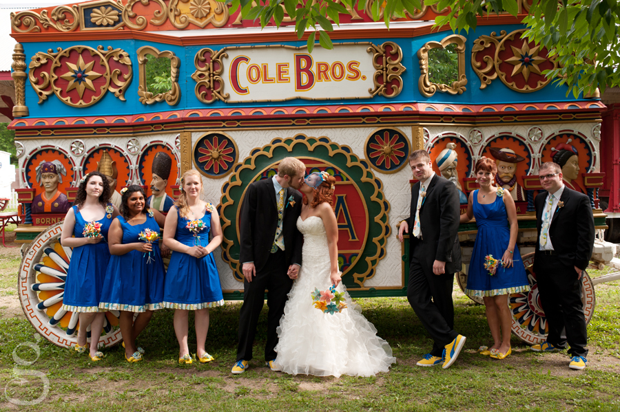 the entire bridal party with their blue dresses and colorful shoes in front of the Cole Bros' circus wagon.