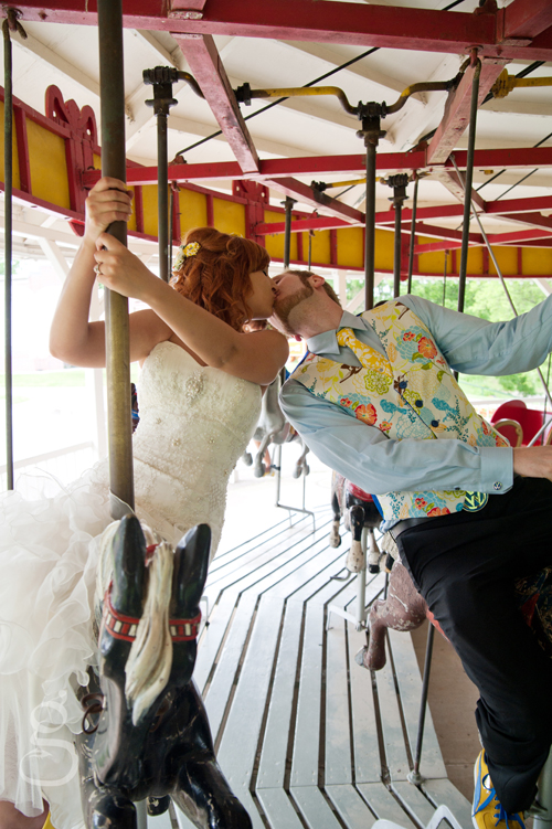 wedding couple kissing on the carousel.