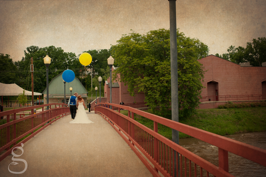 the bride and groom walking across the bridge back to the Circus museum with their giant balloons.