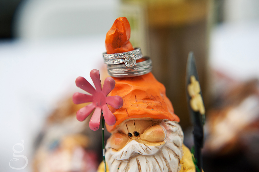 wedding bands on the head of a cute little wooden gnome.