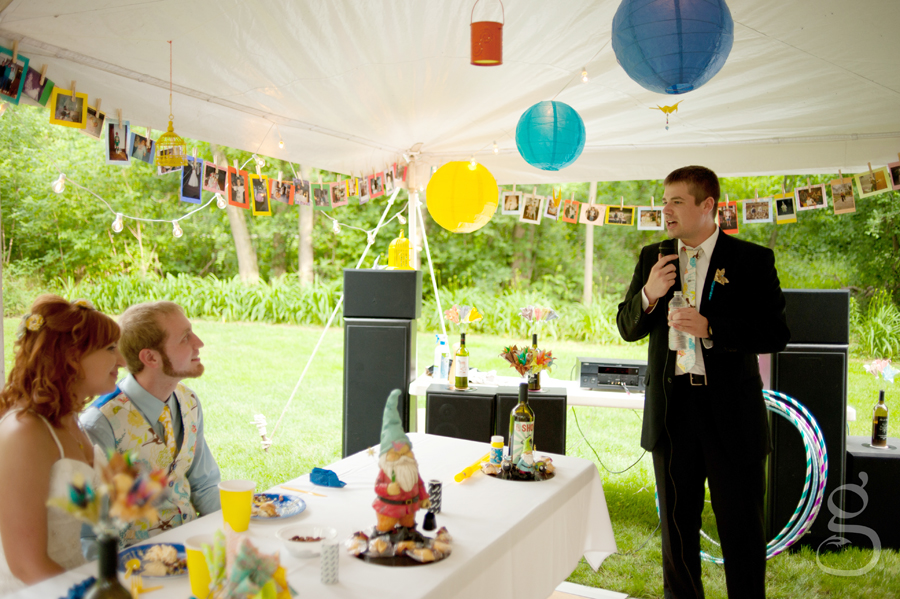 the best man giving a speech to the bride and groom at the reception, under the white tent in the backyard.