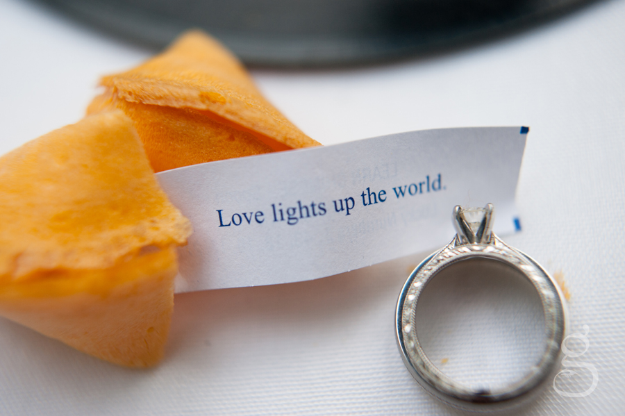 """Love lights up the world"" on the fortune from the fortune cookie with the bride's wedding band on top."
