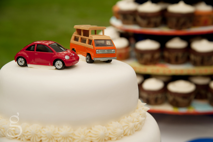 little volkswagon die cast cars as the wedding cake toppers with cupcakes in the background.