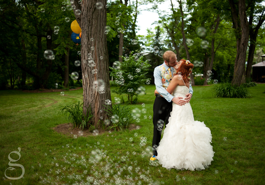the couple kissing underneath a bubble maker in the backyard.