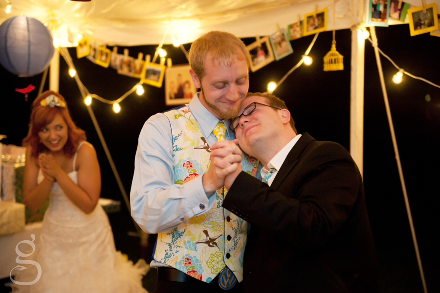 the groom and one of his groomsmen dancing while the bride giggles in the background.