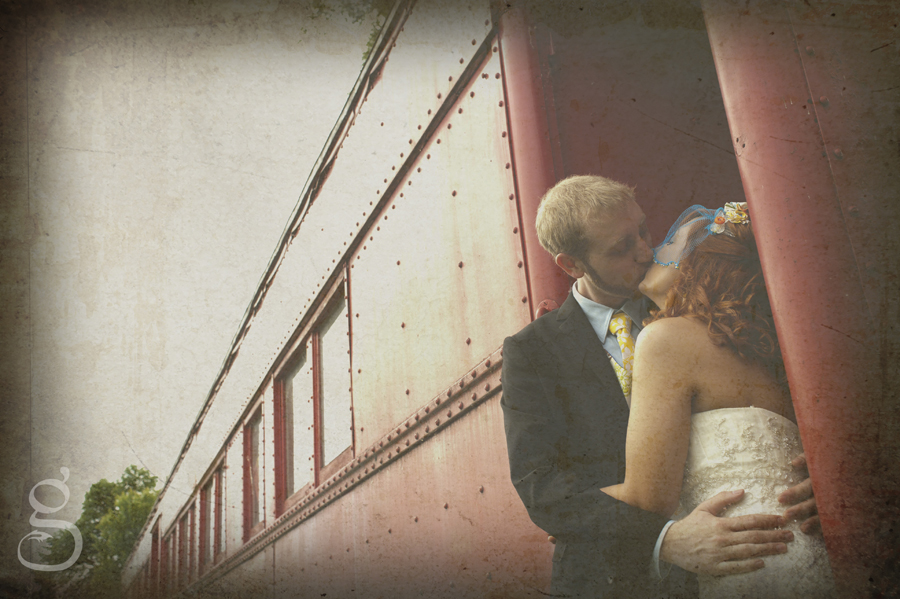 the bride and groom kissing in the doorway of a red circus traincar that was once used for advertising the circus.