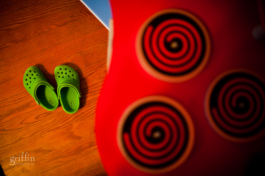 Green crocs on the floor next to the child sized kitchen.