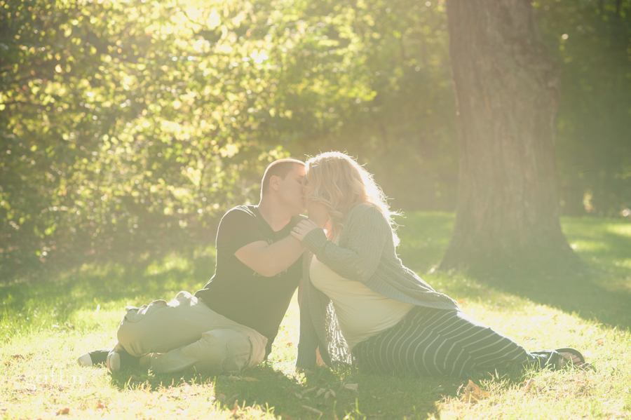 engaged couple sitting on the grass with the light filtering down on them at the lake.