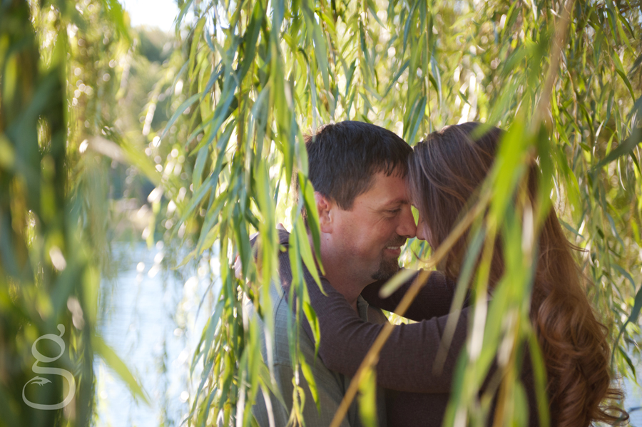 Engaged couple among the falling leaves of a weeping willow tree.