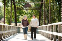 engaged couple hand in hand walking across the wooden bridge at lower Ochsner's Park in Baraboo.