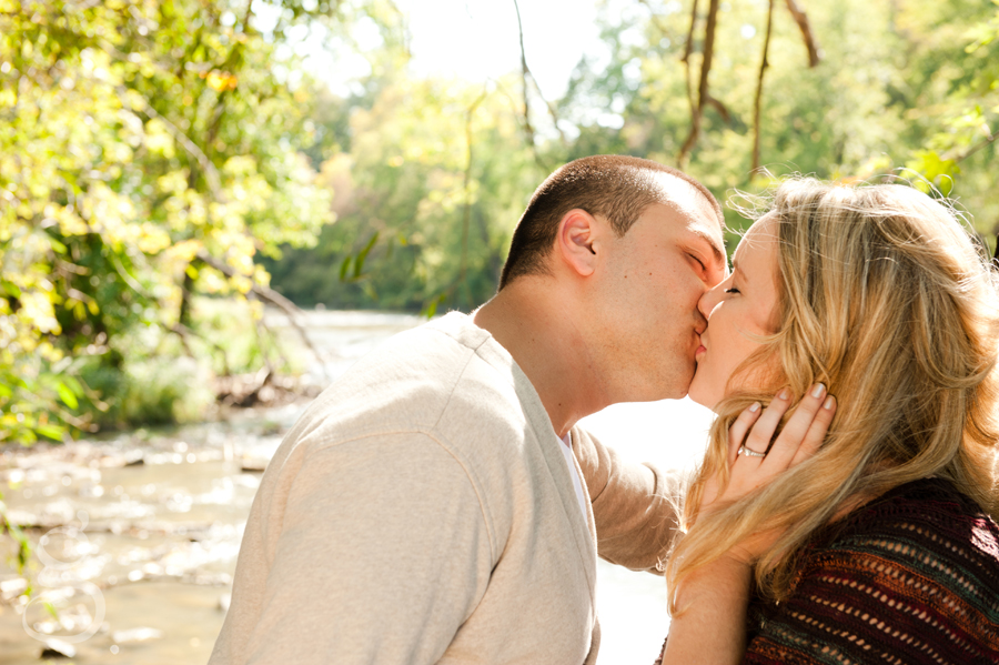 Engaged couple kissing with the Baraboo river flowing behind them as they lean up against a tree.