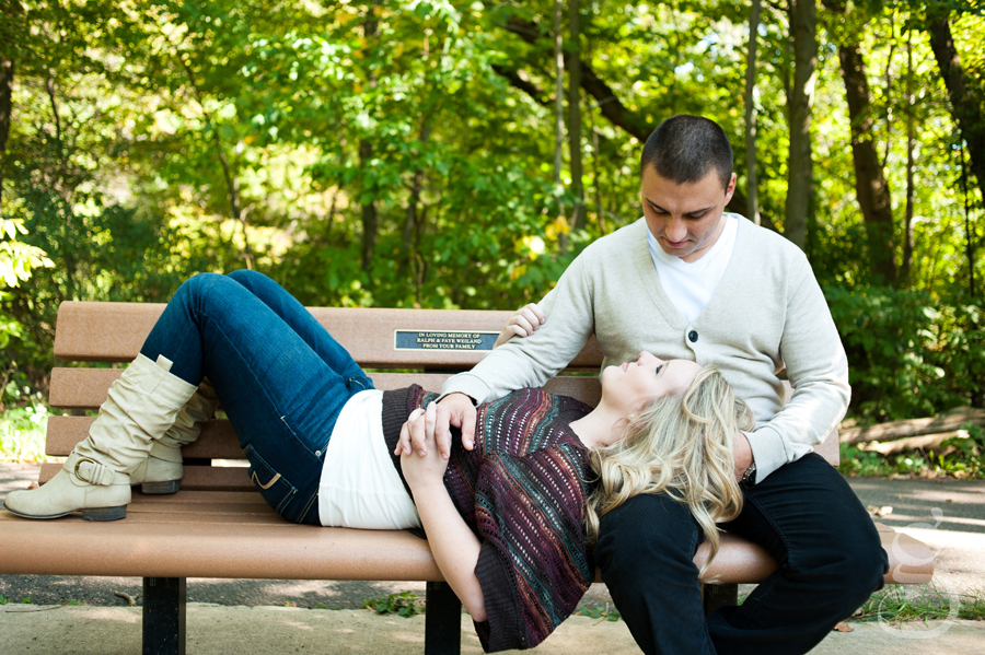 Mandy laying on a park bench looking up at Strash as he holds her hand.