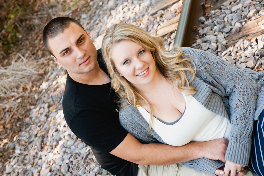 the engaged couple sitting on the railroad tracks and smiling up at the camera at Devil's lake North Shore.