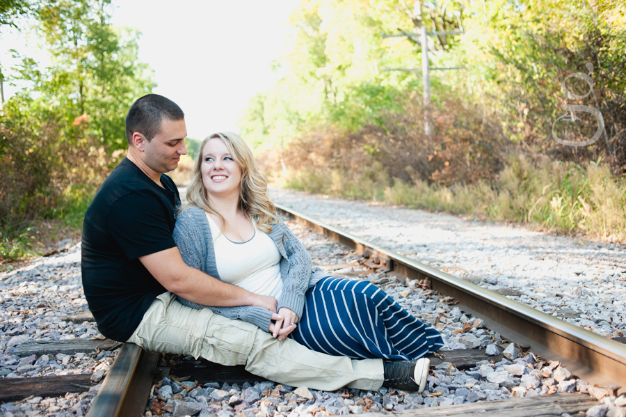 Mandy and Strashe sitting on the railroad tracks looking at one another.