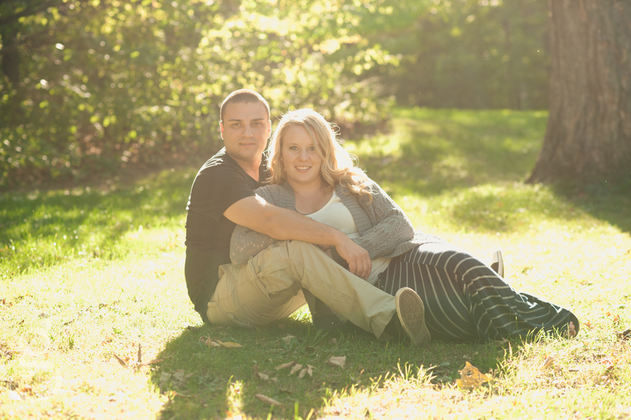 Mandy and Strash sitting on the grass looking at the camera while the sun lights them up.