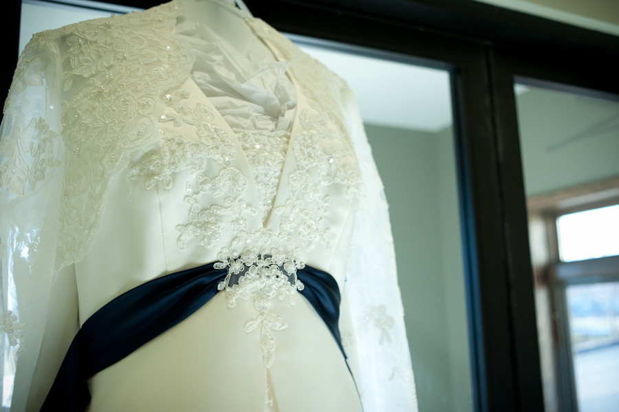 Close up of the lace and blue sash on the wedding gown.