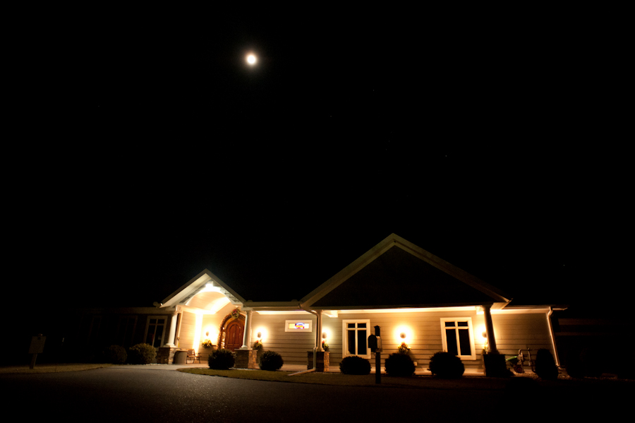 The Baraboo country club all lit up for the night with the moon rising above.