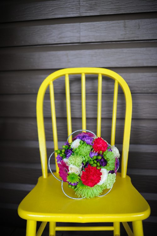 Wedding bouquet on old wooden chair painted yellow.
