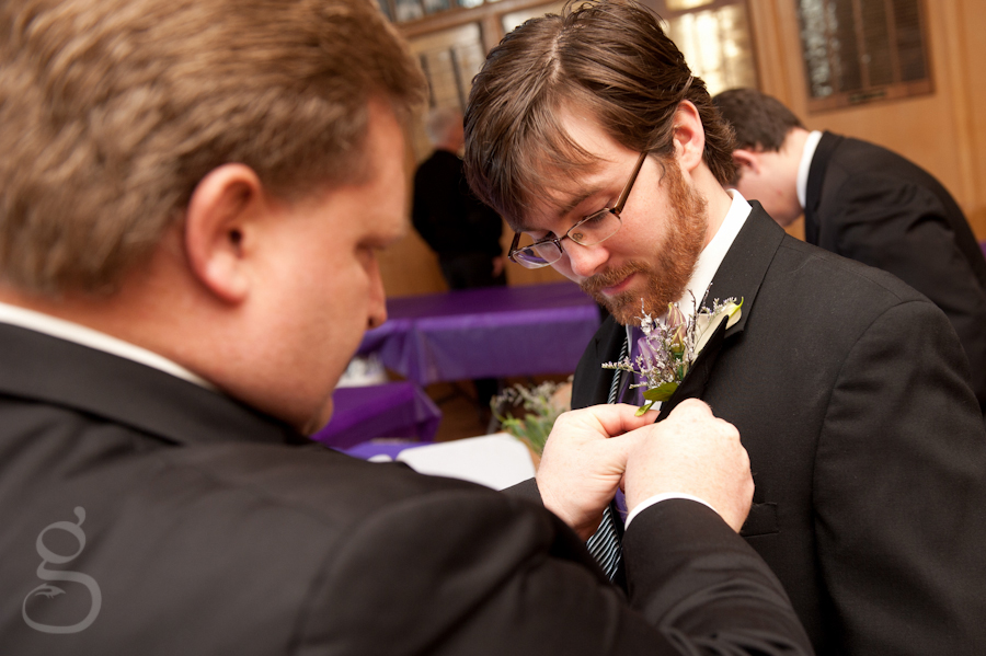 The groom getting his flowers pinned on.