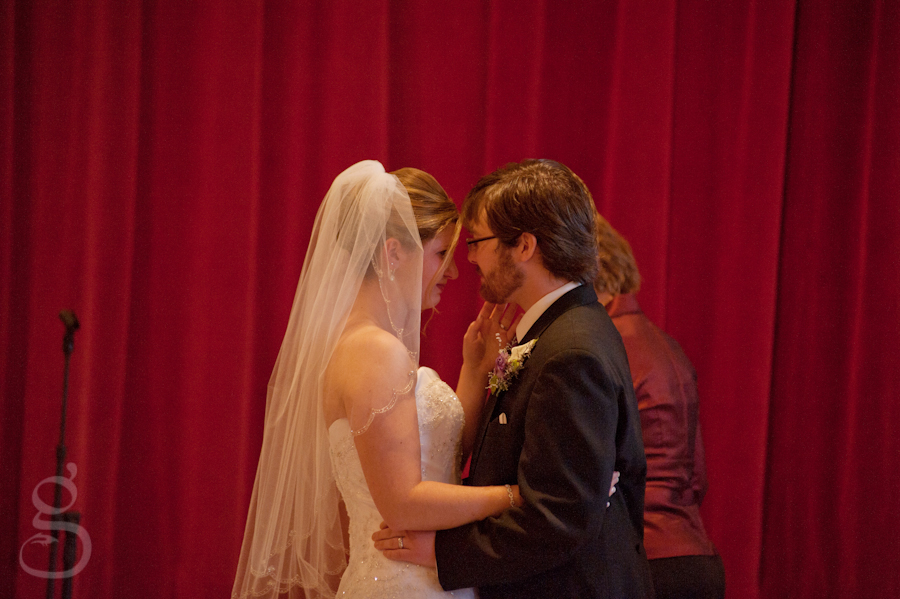 Bride and groom in front of red curtain for the first kiss as man and wife.