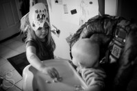 black and white of z in the high chair and j in her lion mask stealing puffs.