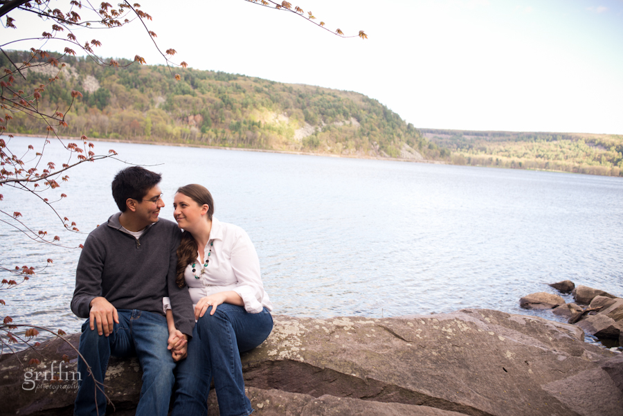 Engaged couple sitting on a rock on the West Bluff Trail at Devil's Lake.