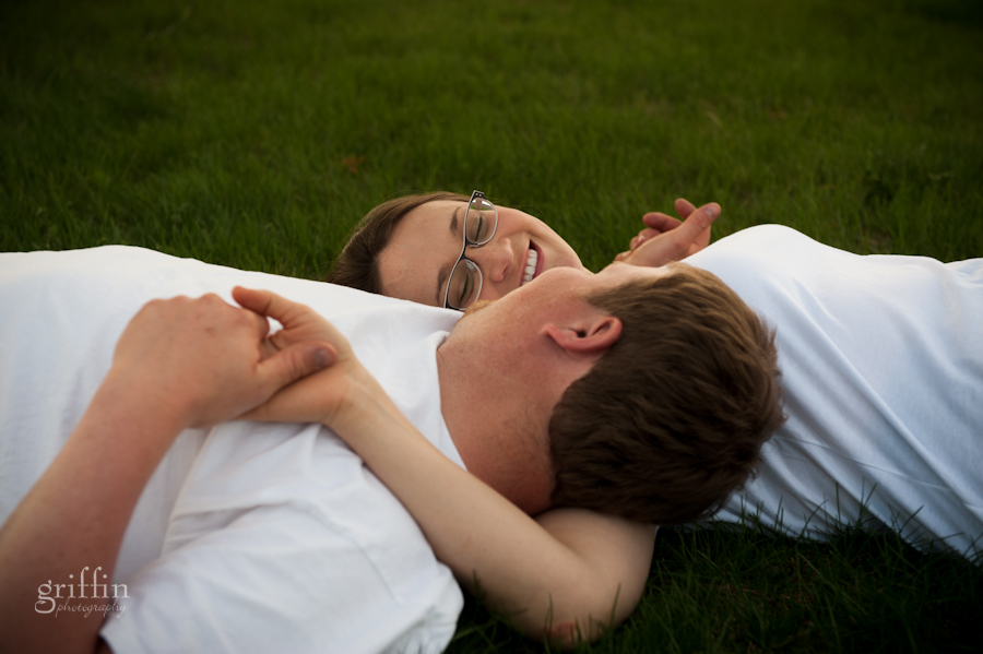 steve and coty laying on the grass looking at one another.