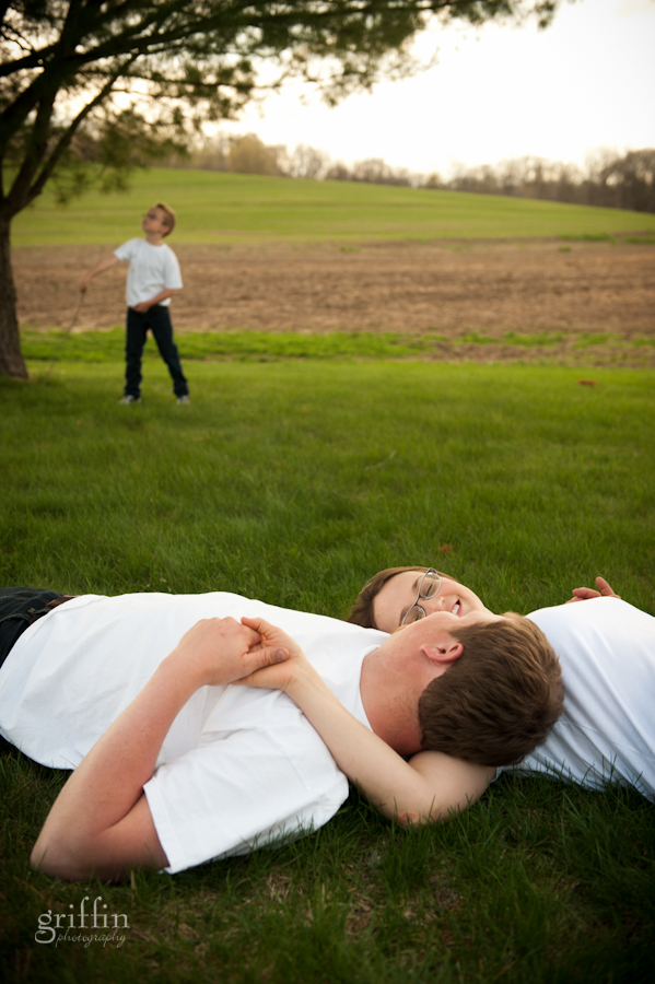 engaged couple laying on the grass while her son plays in the background.