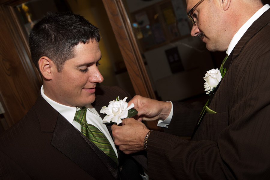 The groom getting his boutoniere pinned on by his father