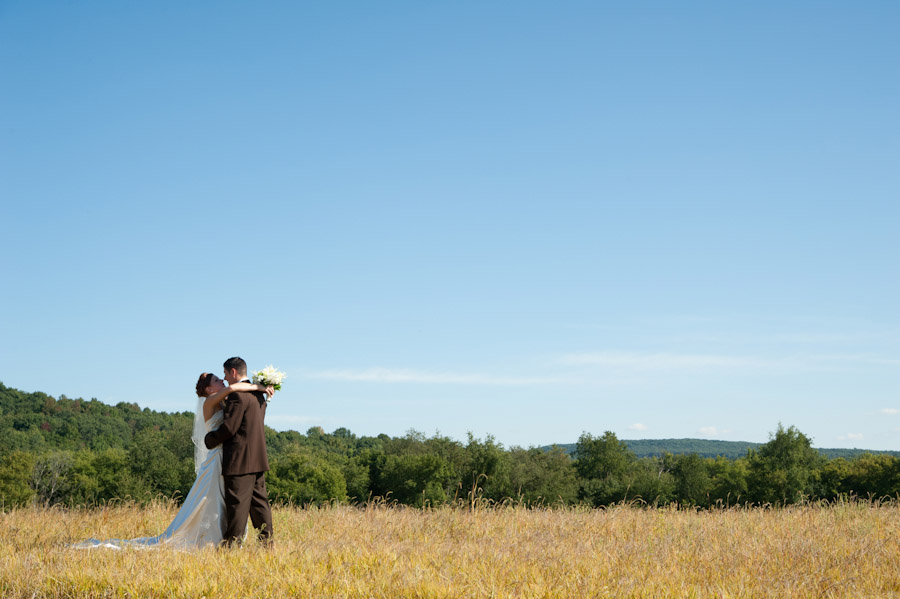 the bride and groom in a field of grass with the blue sky above them
