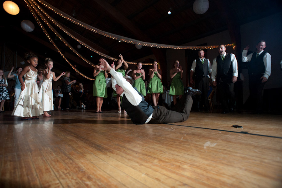 the best man at the wedding doing the worm on the wooden dance floor