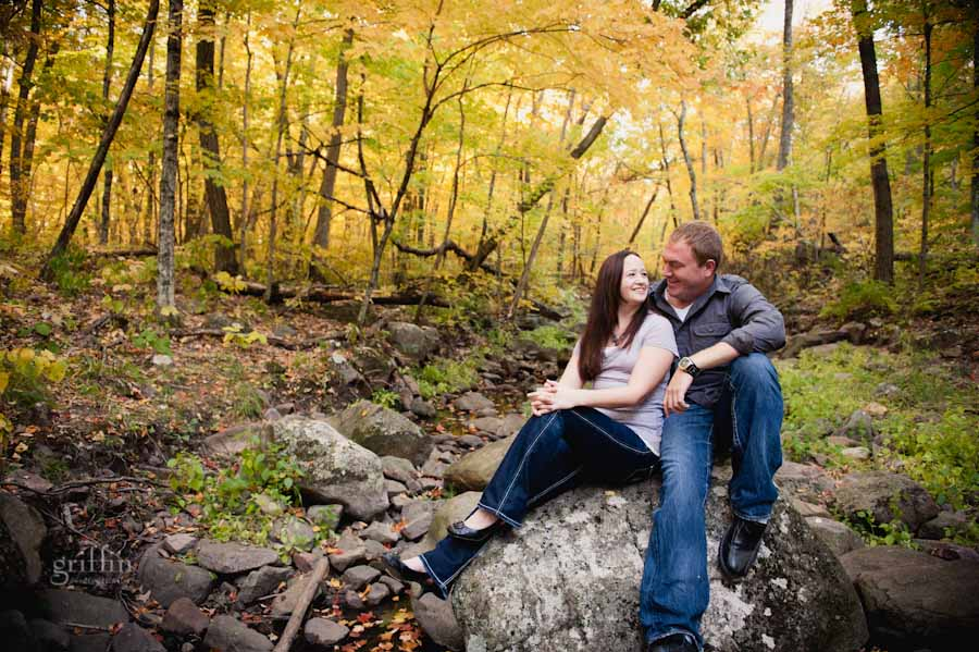 engaged couple sitting on a rock in the empty creek bed
