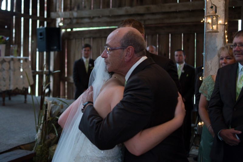 bride and her father hugging at the end of the aisle.