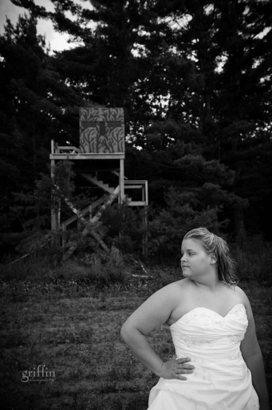 the bride in front of the hunting tower in a field of potatoes.