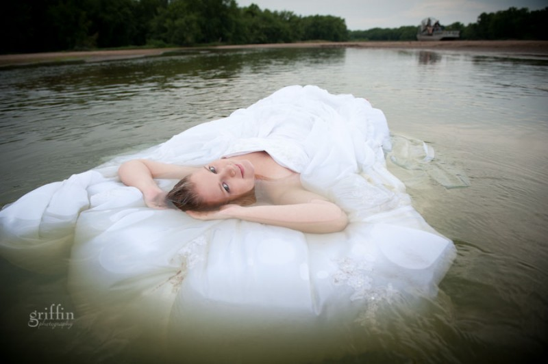 bridal gown in the river flowing behind bride