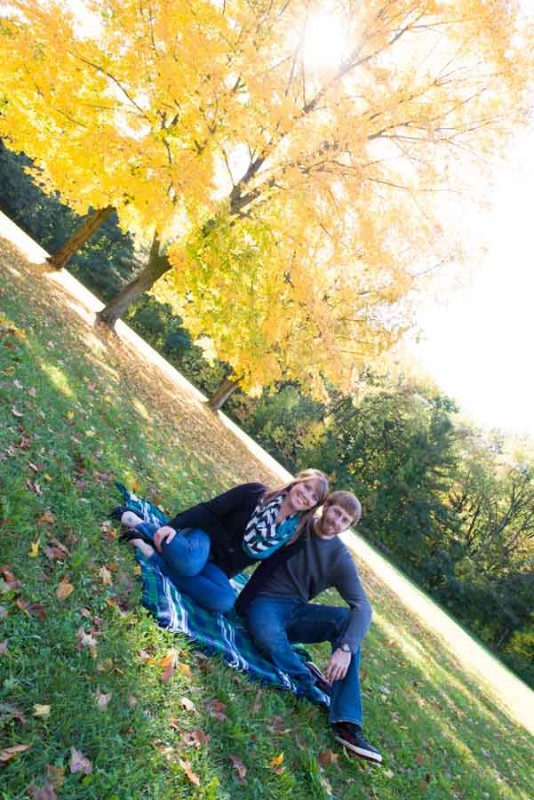 chad and kyra just sitting on a blanket under the beaufiful autumn sun with yellow leaves behind them.