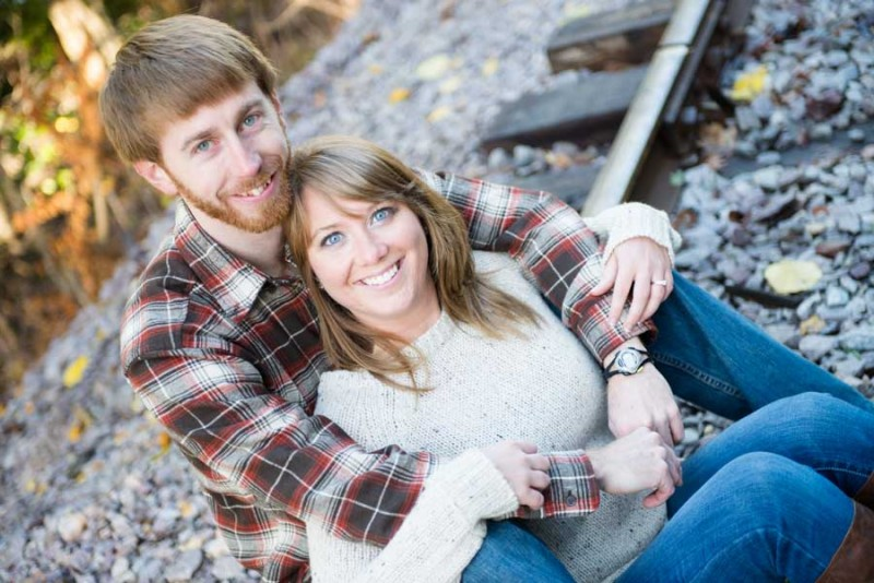 the engaged couple sitting on the railroad tracks