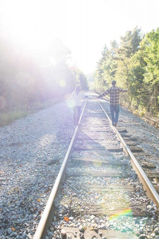 hand in hand walking down the railroad tracks
