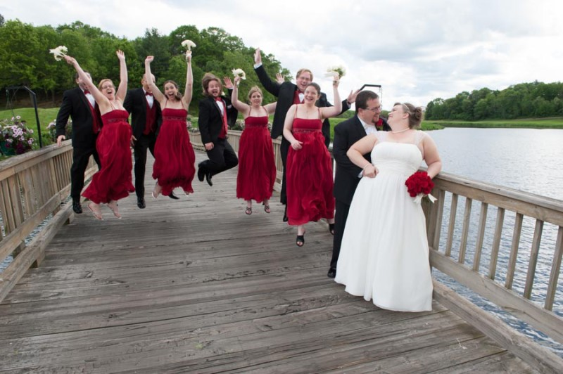 the bridal party jumping up behind the bride and groom at the reception in the Dells.